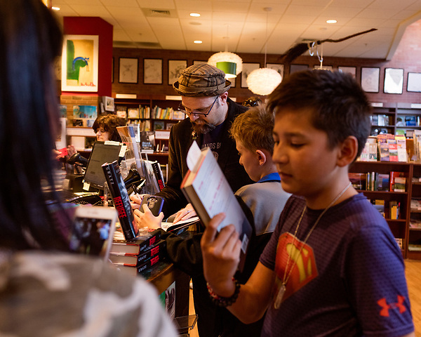 July 26, 2017. Raleigh, North Carolina.<br />  <br /> Alan Gratz signs a book for early arriver Collin Aherne, age 12, who was also vlogging the encounter on his phone. <br /> <br /> Author Alan Gratz spoke about and signed his new book &quot;Refugee&quot; at Quail Ridge Books. The young adult fiction novel contrasts the stories of three refugees from different time periods, a Jewish boy in 1930's Germany , a Cuban girl in 1994 and a Syrian boy in 2015.