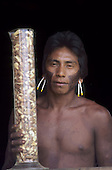 A-Ukre village, Xingu, Brazil. Kayapo man holding a measuring cylinder full of Brazil nuts for the Body Shop; Para State.