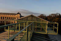 Tropical Rainforest Glasshouse (formerly Le Jardin d'Hiver or Winter Gardens), 1936, René Berger, Jardin des Plantes, Museum National d'Histoire Naturelle, Paris, France. Oblique view from the front of walkways and cupola on the roof of the glass and metal Art Deco style structure lit by the winter early morning light. To the left is the Grand Gallery of Evolution.