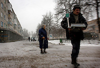 An elderly woman walks while a man carries a scale in the town of Ludinovo, near the city of Kaluga southwest of Moscow. .Picture by Justin Jin.