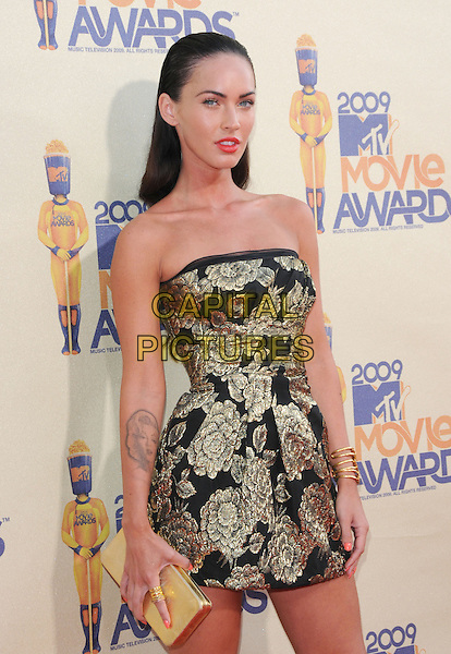 MEGAN FOX.The 2009 MTV Movie Awards held at Universal Ampitheatre  in Universal City, California, USA..May 31st, 2009 .half length black gold floral print strapless dress clutch bag hair slicked back combed tattoo.CAP/DVS.©Debbie VanStory/Capital Pictures.