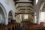 Looking east down the nave towards the altar and east window with historic wooden  pews, roof beams, whitewashed walls with columns, interior of village parish church at Hintlesham, Suffolk, England, UK