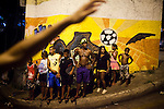 Residents watch a parade during Carnaval in Rocinha, the biggest favela in Brazil, with over 100,000 residents, in Rio de Janeiro, Br., on Thursday, Jan. 24, 2013. In early November 2011 about 3,000 police officers and soldiers moved into one of the largest slums in Latin America in an effort by the Brazilian government to assert control over lawless areas of the city ahead of the 2014 World Cup and 2016 Summer Olympics.