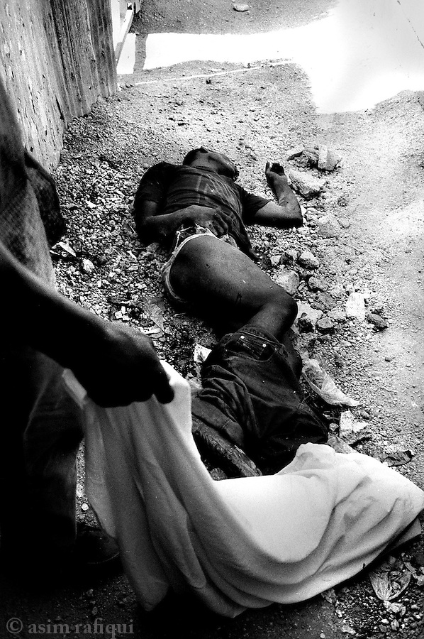 the bullet ridden body of jean michel saint-bert lies in a bel air alleyway is covered by a local resident until it can be taken away to the morgue or the family's home.  jean michel was a victim of a haitian national police death squad operation in the bel air slum on april 28th.  he was repeatedly shot, his head bludgened and his genitals mutilated as an additional humiliation.  jean micheal was a lavalas activist from bel air<br />
