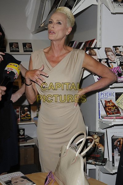 BRIGITTE NIELSEN.Brigitte Nielsen launches her new book 'You Only Get One Life' at the London Book Fair, Earls Court, London, England..April 11th, 2011 .half length dress sleeveless beige hand on hip funny .CAP/CAN.©Can Nguyen/Capital Pictures.