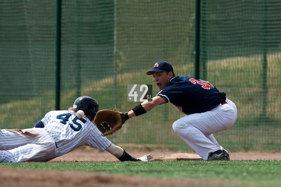 23 May 2009: Jean-Pascal Furet of La Guerche stretches for the ball as Luc Piquet slides back into first base during the 2009 challenge de France, a tournament with the best French baseball teams - all eight elite league clubs - to determine a spot in the European Cup next year, at Montpellier, France. Rouen wins 6-2 over La Guerche.