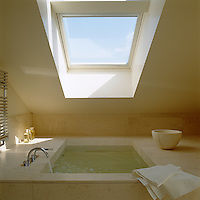 In a minimal yet luxurious bathroom the sunken marble bath has been placed directly below a large skylight