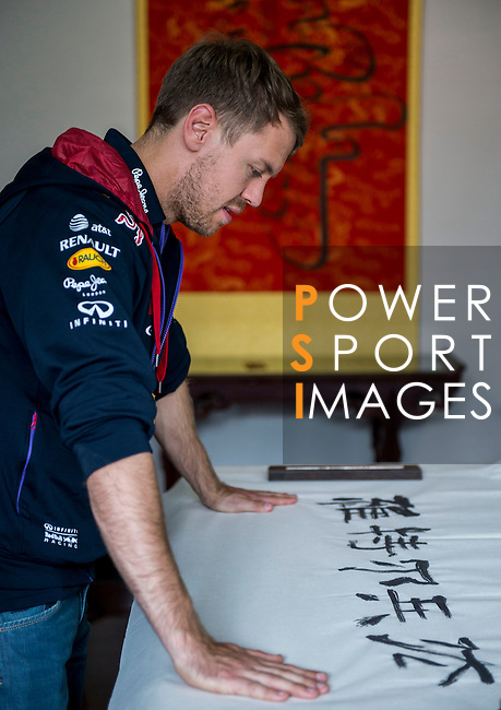 Infiniti Red Bull Racing driver Sebastian Vettel  of Germany is pictured during the filming of a viral video learning Chinese calligraphy with Han Bo Yun master on April 21, 2014 in Beijing China. Photo by Victor Fraile / Power Sport Images