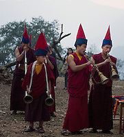 Buddhist monks playing uniue Sikkimese musical instruments during the Losar New Year ceremony at a monastery in the Himalayan foothills of Sikkim, India