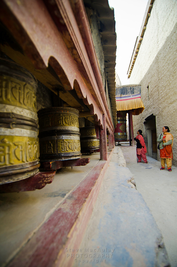 Ladakhi women spinning prayer wheels, Shey Palace, Naropa Royal Palace, in Ladakh, India.