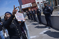 Baltimore, MD - April 25, 2015: A woman holds a sign as she gathers with hundreds of protestors near the Baltimore Police Department's Western District Headquarters April 25, 2015 to demand police accountability in the death of Freddie Gray and protest police brutality. Gray died of a broken spine while in police custody.  (Photo by Don Baxter/Media Images International)