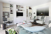 A smart living area adjoins the kitchen/dining area in the open-plan apartment, furnished with a subtly retro range of furniture and practical built-in shelving