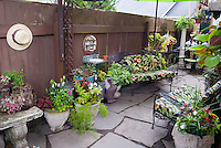 Flea market and antique ornamented small garden. Tiny water feature using old sink and mirror, pots in containers, small garden, Adorable garden fountain made from an old sink