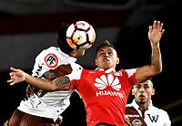 BOGOTA - COLOMBIA - 20 - 02 - 2018: Juan Roa (Der.) jugador de Independiente Santa Fe, salta a cabecear el balón con Enzo Gutierrez (Izq.) jugador de Santiago Wanderers, durante partido de vuelta entre Independiente Santa Fe (COL) y Santiago Wanderers (CHL), de la fase 3 llave 1, por la Copa Conmebol Libertadores 2018, jugado en el estadio Nemesio Camcho El Campin de la ciudad de Bogota. / Juan Roa (R) player of Independiente Santa Fe jumps to head the ball with Enzo Gutierrez (L) player of Santiago Wanderers, during a match for the second leg between Independiente Santa Fe (COL) and Santiago Wanderers (CHL), of the 3rd phase key 1, for the Copa Conmebol Libertadores 2018 at the Nemesio Camacho El Campin Stadium in Bogota city. Photo: VizzorImage  / Luis Ramirez / Staff.