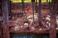 A woman sits in meditation under a grove of trees near a stream in Waimanalo, Oahu.