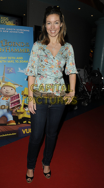 EMMA CROSBY .Attending the film premiere of 'Bob the Builder: The Legend of the Golden Hammer' at Vue West End cinema, Leicester Square, London, England, May 15th 2010. .arrivals full length jeans green top print blue floral wrap peep toe shoes black hand in pocket smiling  .CAP/CAN.©Can Nguyen/Capital Pictures.