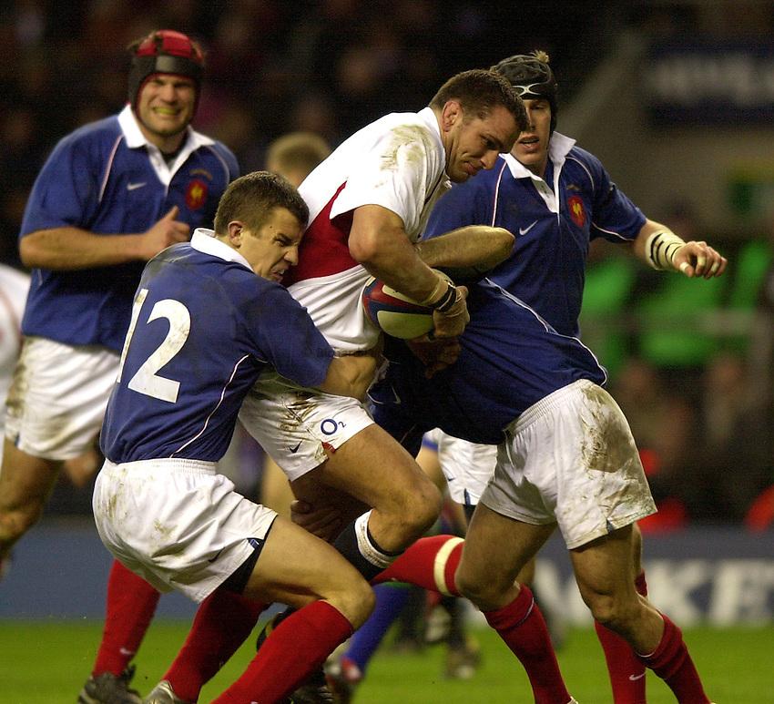 Photo. Richard Lane. .England v France at Twickenham. RBS Six Nations Championship. 15/02/2003.Martin Johnson attacks as Damien Traille tackles.