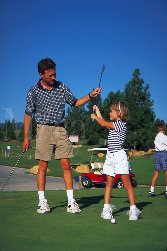 Father teaching daughter how to golf