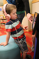NWA Democrat-Gazette/MARY JORDAN @NWAMARYJ  Benjamin Mason, 3, of Hiwasse is assisted on a children's iPad by his mother, Kirsten, Thursday at the Bentonville Public Library.
