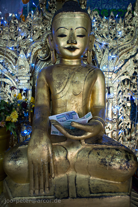 Buddha  spirit with money attached as offering in shrine at Mount Popa temple area, Myanmar, 2011