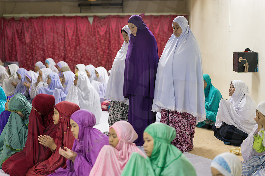 January 10, 2015 - Rawang (Malaysia). Dr. Azlina Jamaluddin (wearing a purple dress) during the Maghrib prayer with other Global Ikhwan members. Dentist at the company's Clinic in Rawang, she was one of the Obedient Wives Club Organiser. Educated in Australia she joined the company in 2001. © Thomas Cristofoletti / Ruom