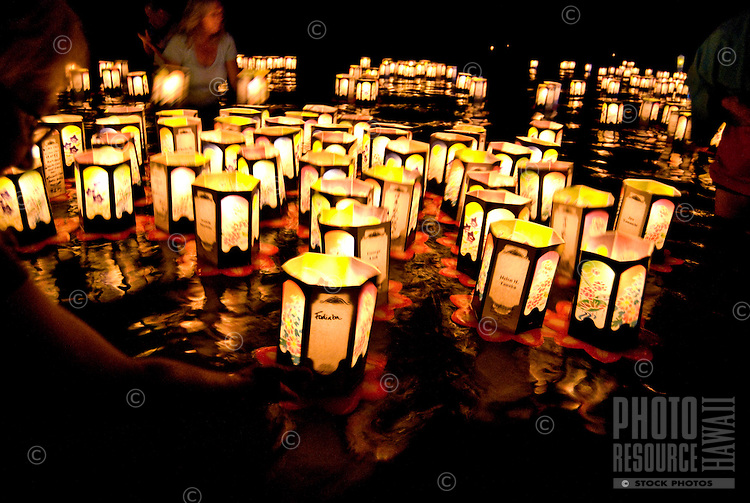 A woman releases a paper lantern inscribed with the name of her loved one among the hundreds launched at the the annual bon dance and Toro Nagashi (ìfloating lanterns set out to seaî) ceremony in Haleiwa. Inscribed with the names of the departed, th