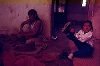 Working all day making pottery in her home, Isidra Carballido is a contrast to her six year-old grand daughter Cecilia Mateos dressed in her modern clothing. The small village where they live is known for black pottery that turns dark when fired in a pit kiln because of the iron oxide in the local clay. They buy barro (black earth) and soak it in water for four days. It is filtered and then molded by hand and then dried.