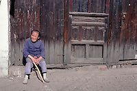 An old woman enjoys the November sun outside her traditional wooden house in  Suzhou. Even with her diminutive height, she has to duck in order to pass through her front door.