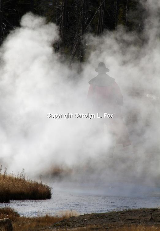 A man walks through smoke in Yellowstone.