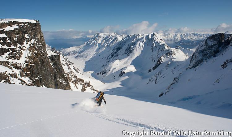 Mann kjører ski ned brearm fra Øksfjordjøkelen mot Nuvsvåg. ---- Man skiing down glacier Øksfjordjøkelen.