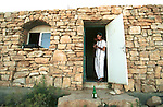 A settler begins to pray, standing at the entrance to the synagogue of the unauthorized Israeli outpost of Tekoa D, West Bank.