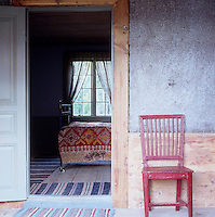 A red painted chair stands in a corridor beside the open doorway into a bedroom