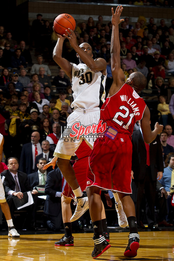 Travis McKie #30 of the Wake Forest Demon Deacons shoots over C.J. Williams #21 of the North Carolina State Wolfpack at the LJVM Coliseum on January 14, 2012 in Winston-Salem, North Carolina.  The Wolfpack defeated the Demon Deacons 76-40.  (Brian Westerholt / Sports On Film)