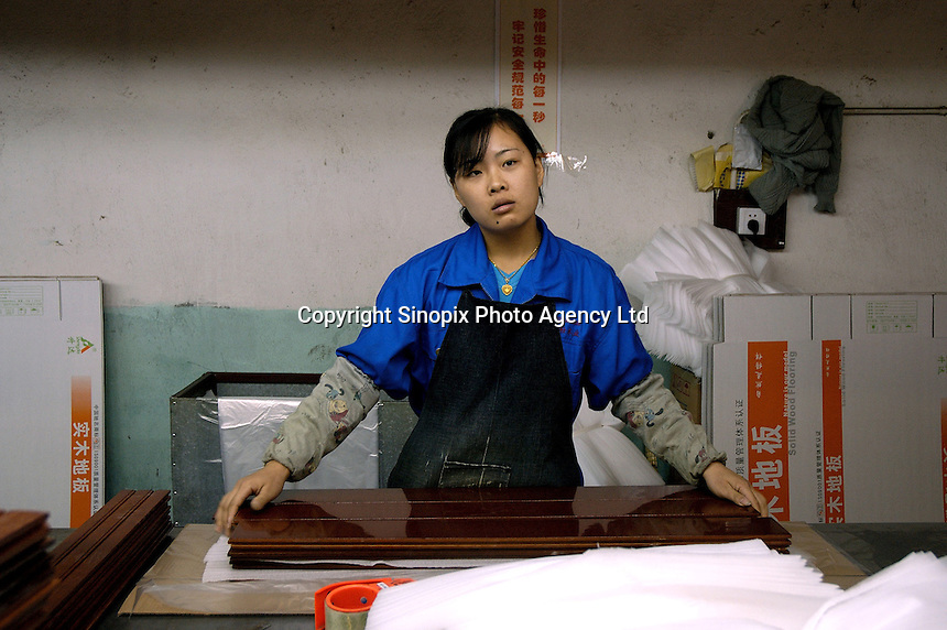 Female worker in packing department of Hong Qi wood floor factory, a private firm which produces floor boards for the booming domestic market and for export to Europe (including UK) and the United States, using wood imported from Asia and South America.