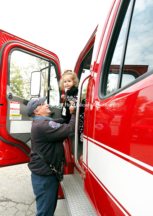 Torrington, CT-14 October 2012-101412CM05-  Lt. Richard Meyer of the Torrington Fire Department sits his granddaughter, Ellie Hudson, 18mo, of Bristol inside of a tactical operation firetruck during an open house Sunday afternoon in Torrington.  The event was held to educate the public on the various roles the fire department plays in serving the public said Fire Chief Gary Brunoli.  The day included tours of the fire house, a smoke trailer, demonstrations from the rope tower and Hazmat trailers.  Campion Ambulance, the State Animal Rescue Team and approximately 30 Torrington Firefighters were apart of the event.  Christopher Massa Republican-American