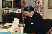 United States President Ronald Reagan signs H.J. Resolution 523 in his study in the Residence of the White House in Washington, D.C. on Friday, April 1, 1988.  The resolution provides for a transfer of 47.9 million U.S.  dollars from the Department of Defense (DoD) to the Agency for International Development (AID), plus an un-specified amount for transportation costs associated with providing assistance, to support peace and democracy in Central America.Mandatory Credit: Bill Fitz-Patrick - White House via CNP