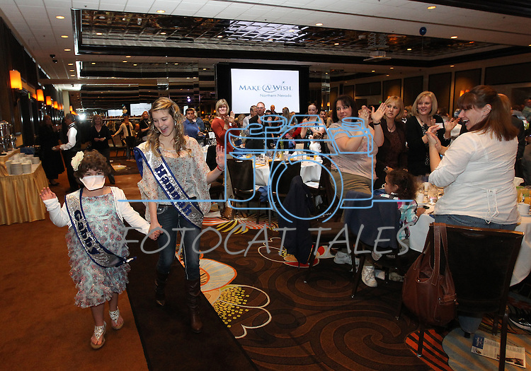 Gabby Gouldsmith, 8, receives a standing ovation as Hannah Hurley escorts her into the Make-A-Wish Foundation Waffles & Wishes event at the Atlantis Casino Resort, in Reno, Nev., on Tuesday, March 27, 2012. Gouldsmith, who suffers from an auto-immune deficiency disorder, received a bedroom makeover from the organization..Photo by Cathleen Allison