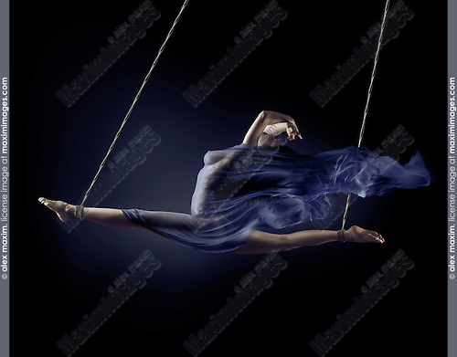 Surreal art nude photo of a beautiful naked woman suspended in a split with bondage ropes by her ankles with flowing cloth wrapped around her nude body on black background