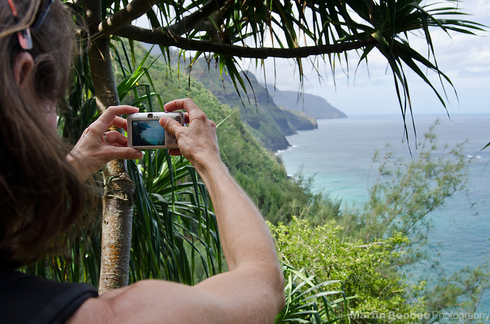 Woman taking pictures of the Na Pali Coast from the Kalalau Trial, Kauai, Hawaii
