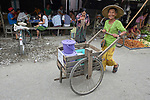 A woman pushes a cart through the Tahan Market in Kalay, a town in Myanmar. This market is located in Tahan, the largely ethnic Chin section of the town.