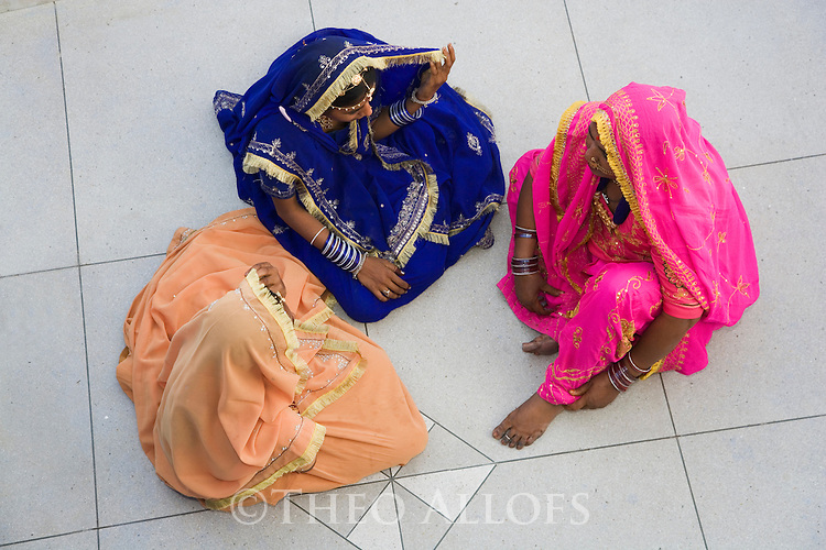 Rajasthani women in traditional colorful dresses sitting on marble floor, Jodphur, Rajasthan, India --- Model Released