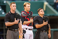 Lansing Lugnuts catcher Ryan Hissey (15) is flanked by umpires Tom Hanahan (L) and Isaias Barba (R) during the national anthem before the game against the South Bend Cubs on May 12, 2016 at Cooley Law School Stadium in Lansing, Michigan. Lansing defeated South Bend 5-0. (Andrew Woolley/Four Seam Images)
