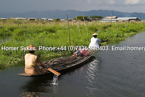 Inle Lake. Myanmar (Burma.) 2006. Two women rowing home in their flat bottomed boat. A young child with traditional thanakha sits amongst the wooden sticks they have collected.