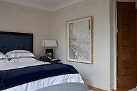 A large painting of a bed hangs on the wall beside the bed in the master bedroom