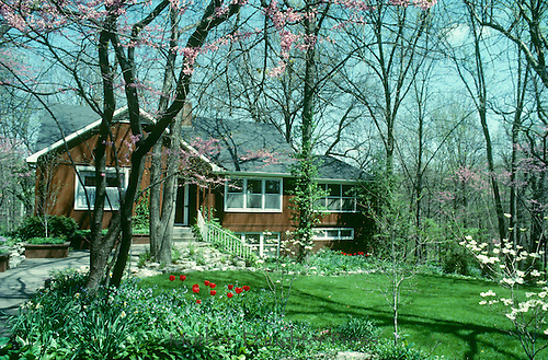 Cedar wood house midwest in mature neighborhood with trees and green space,  spring midwest.  Blooming annuals and perennials. Decking and landscape make an inviting front entrance.