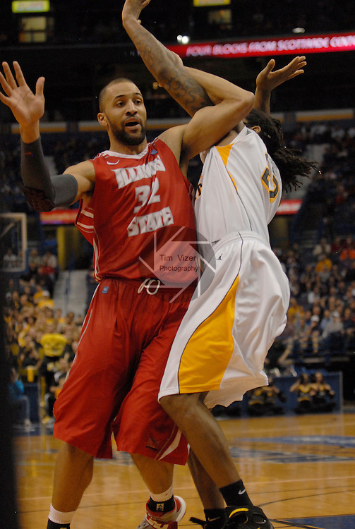 Illinois State Redbirds forward Jackie Carmichael (32) is tangled up with Wichita State Shockers forward Carl Hall (22) as he tries to receive an inbound pass in the second semifinal game of the Missouri Valley Conference Tournament. The Illinois State Redbirds played against the Wichita State Shockers on Saturday March 9, 2013 at the Scottrade Center in St. Louis, Missouri.