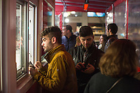 Felipe Francisco, of Boston, places an order at the outside take-out window at Tasty Burger on Boylston Street in the Fenway neighborhood of Boston, Massachusetts, USA, in the early hours of Saturday, Dec. 5, 2015. Francisco and friends were on a bar crawl in the area and stopped at Tasty Burger to eat.