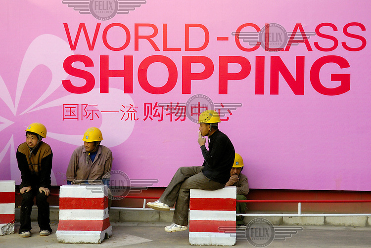 Migrant workers smoke cigarettes during a break on a luxury shopping mall construction site in the Chaoyang district.