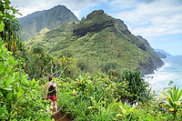 A hiker on the Kalalau Trail looking at Na Pali coastline on Kaua'i.