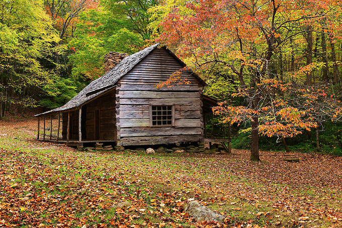 An old cabin framed by colorful Autumn foliage along the Roaring Forks trail in the Smoky Mountains.